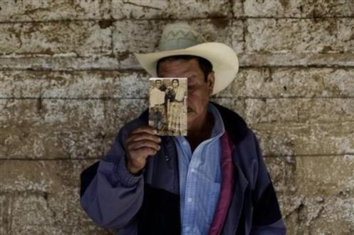 Gaudencio Atz Apir holds a photograph of himself with his wife Maria Natalia Alvarez Ajobal before she was hung in 1981 by the Guatemalan Army during a massacre in Pachay las Lomas village in Chimaltenago, Guatemala
